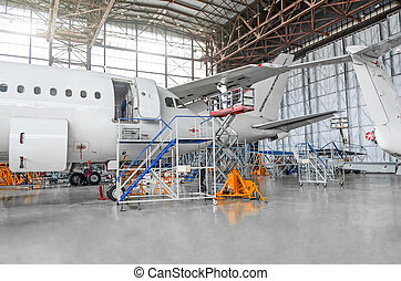 Passenger aircraft for maintenance of repair in the aviation hangar.