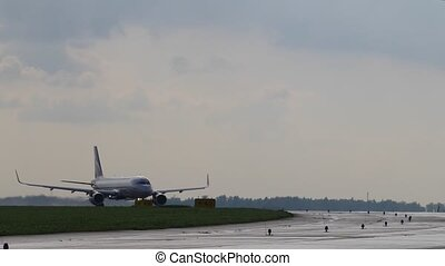 Passenger aircraft moves on runway. Airplane before takeoff. Cloudy sky