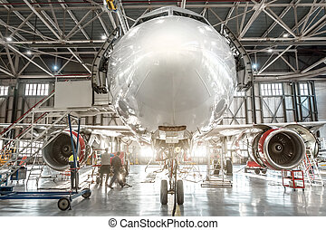 Passenger aircraft, nose close up. Maintenance of engine and fuselage repair in airport hangar