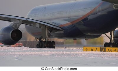 Passenger aircraft on a snowy runway - Long shot of a...