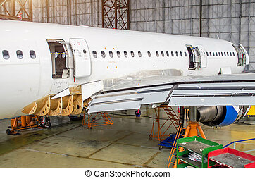 Passenger aircraft on maintenance, a view of the rear of the fuselage in airport hangar.