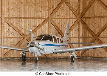 Passenger aircraft on maintenance. Aircraft parcked in hangar. Aircraft during maintenance. Woden hangar at airport.