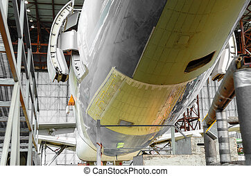 Passenger aircraft on maintenance and fuselage repair after damage in airport hangar.