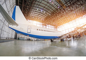Passenger aircraft on maintenance of engine and fuselage repair in airport hangar. Rear view, under the tail.