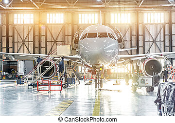 Passenger aircraft on maintenance of engine repair in airport hangar.