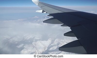 Passenger aircraft wing against distant mountains
