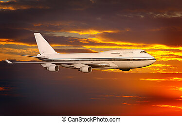 passenger airplane in the clouds at sunset or dawn.
