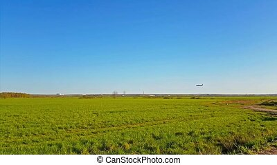 Passenger airplane is landing at the international airport Pulkovo, St. Petersburg, Russia. Large airliner is flying in the sky over a green field. Industrial and civil air transportation by air