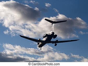 Passenger airplane landing in sunset beams