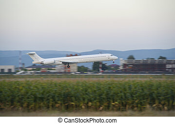 Passenger airplane landing on runway at dusk hour