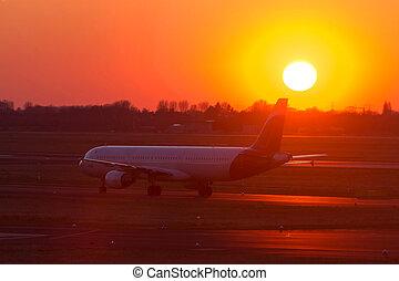 passenger airplane on an airport runway in an evening sundown