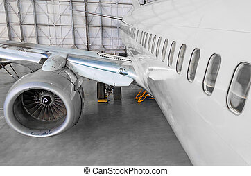 Passenger airplane on maintenance of jet engine and aircraft hangar.