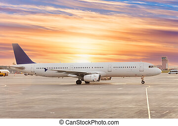 Passenger airplane on runway near the terminal in an airport at sunset time.
