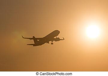 passenger airplane starting in the evening sun