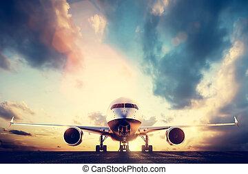 Passenger airplane taking off on runway at sunset
