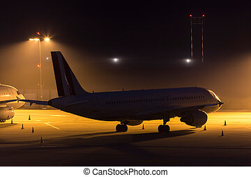 passenger airplane waiting on an aiport at night