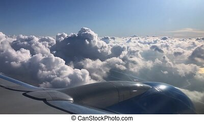 Passenger airplane window view dropping through beautiful fluffy clouds