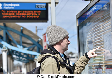 Passenger at timetable on a Russian commuter train station