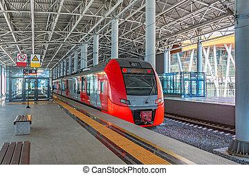 Passenger commuter train on station platform awaiting passengers.