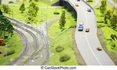 passenger express train moves on rail in modern toy city among roads with small cars and trees