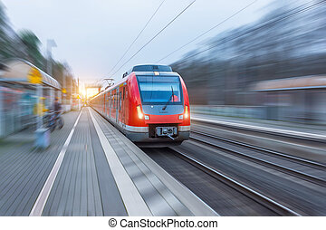 Passenger high speed red train with motion blur in station.