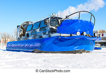 Passenger hovercraft transporter on the ice of river in winter day