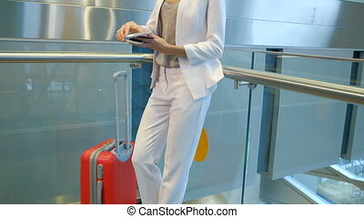 Passenger in a white pantsuit checks the tickets before...