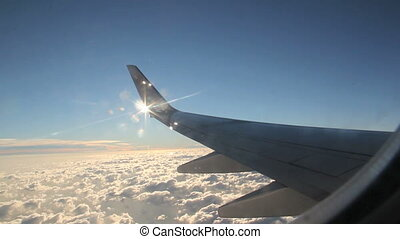 Sun breaks through from behind the wingtip of a passenger jet in flight.