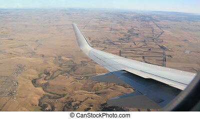 Passenger jet in flight banks to the right as the wing rises above the horizon.