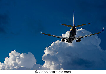 Passenger jet landing against a blue sky with white fluffy clouds