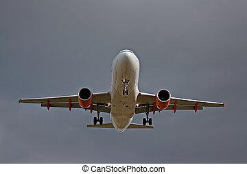Passenger jet landing against a grey sky