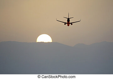 passenger jet plane flying in the evening sky at sunset
