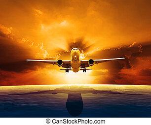 passenger jet plane flying over beautiful sea level with sun set