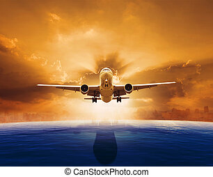 passenger jet plane flying over beautiful sea level with sun...
