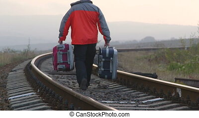 Passenger man with suitcases walking away on railway track