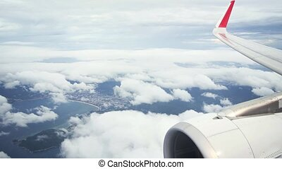 Dramatic aerial view of Patong Beach in Thailand, from a passenger perspective with engine and wingtip in frame and fluffy clouds below.