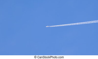 Passenger Plane Flies in the Clear Sky Leaving behind a Smoke Trail