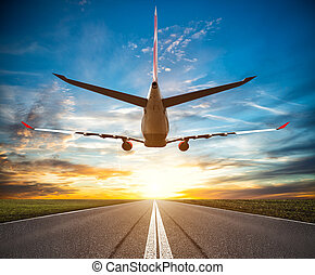 Passenger plane fly up over take-off runway at sunset....