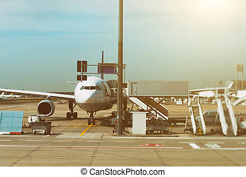Passenger plane in the airport at sunrise. Aircraft maintenance.