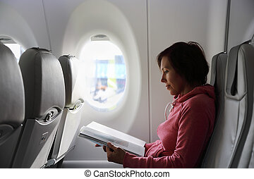 Passenger reads a magazine in the aircraft
