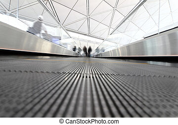 passenger rushing through an escalator in airport terminal