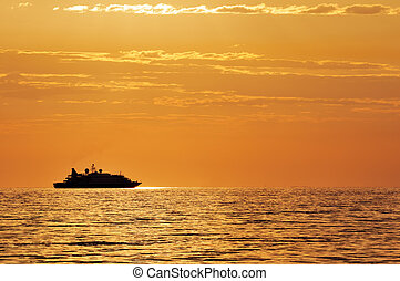 Passenger ship at sunset - Boat silhouette on a quiet sea at...