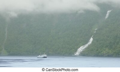 Passenger ship float on lake near mountain with waterfall