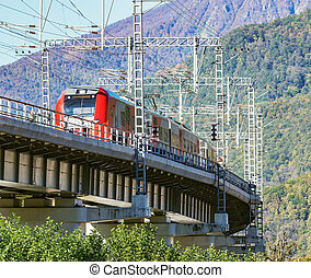 Passenger train from Sochi moves on the bridge.. Krasnaya Polyana. Russia.
