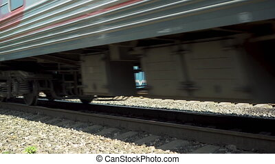 Passenger train is passing by. Side view of the wheels. Rail transport to transport people.