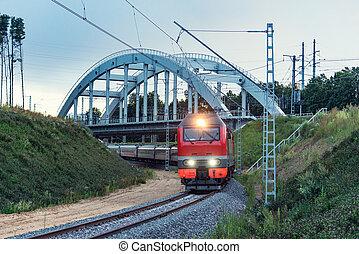 Passenger train moves inder the bridge at evening time.