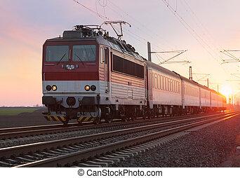 Passenger train on railway at sunset