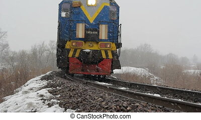 Passenger train on the railway in the winter woods.