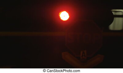 Passenger train passing through rail crossing at night. Traffic light signal.