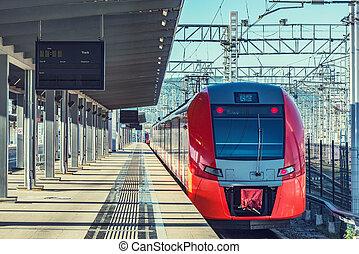 Passenger train stands along the platform.
